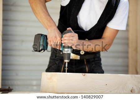 Carpenter drills a hole with an electrical drill - stock photo