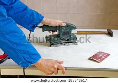 carpenter grinding the surface of a piece of furniture - stock photo