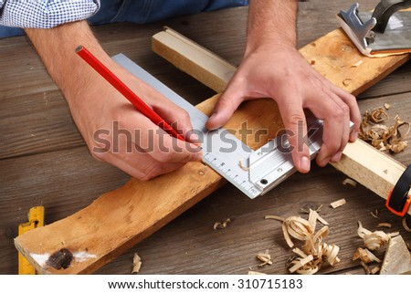 carpenter hand with square and pencil - stock photo