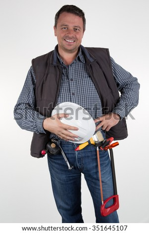 Carpenter in tool belt closeup holds tools over white background - stock photo