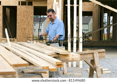 Carpenter inspecting wood before selecting the next support beam - stock photo