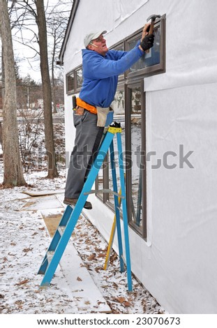 Carpenter installing windows in an addition - stock photo