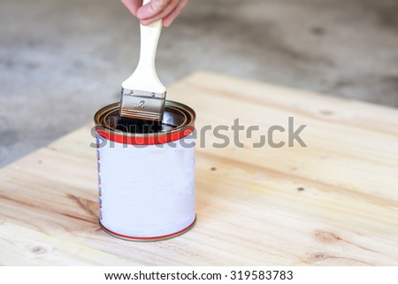 Carpenter is soaking his brush into the can of paint. - stock photo