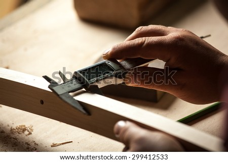 Carpenter measuring chair part with electric calipers in workshop. - stock photo