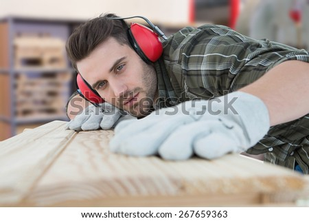 Carpenter measuring wooden plank against workshop - stock photo
