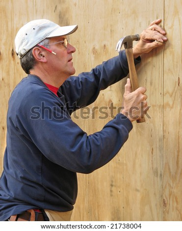 Carpenter nailing plywood sheathing into place - stock photo