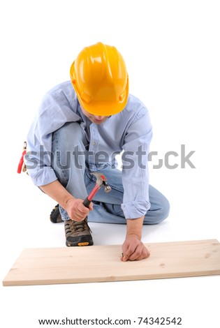 Carpenter nailing the wall with hammer isolated on white - a series of CONSTRUCTION IMAGES. - stock photo
