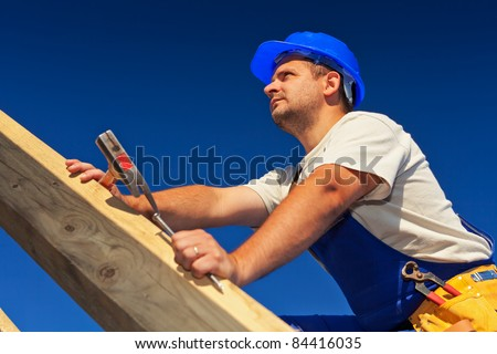 Carpenter on top of roof structure inspecting the building - stock photo