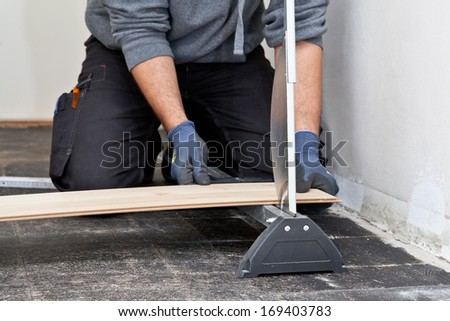 Carpenter or builder measuring and cutting a new wooden floor board for installation during renovation or construction of a building - stock photo