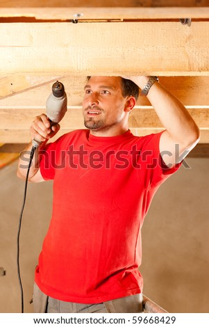 Carpenter or construction worker with hand drill working in the roof framework inside a house - stock photo