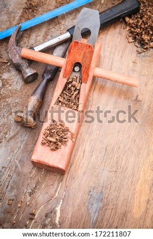 carpenter plane on the old wood with hammer , chisel and saw  - stock photo