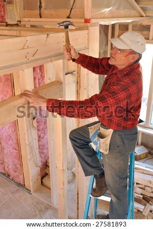 Carpenter pounding a nail into an interior partition - stock photo