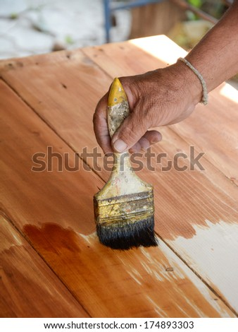 carpenter s hands paintbrush varnish  to wood table - stock photo