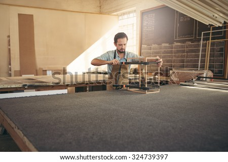 Carpenter's workshop with a craftsman building a display case from wood and glass