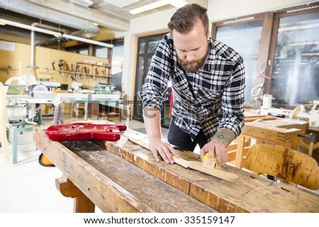 Carpenter sanding a wooden guitar neck in workshop - stock photo