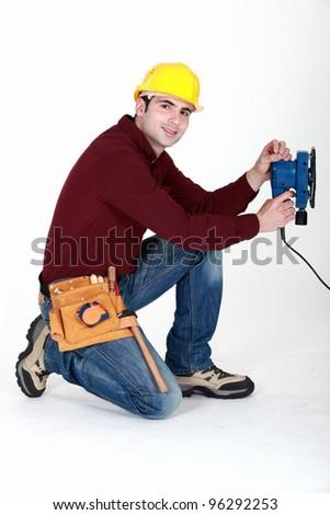 Carpenter saving time by using electric sander - stock photo