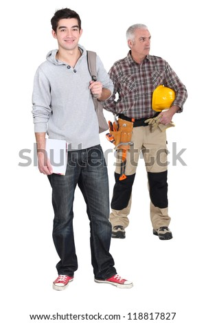 Carpenter stood with young male trainee - stock photo