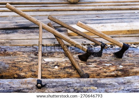 carpenter tools-axes on a background of lumber - stock photo