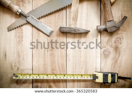 carpenter tools,hammer,meter,nails, and chisel on wooden background. - stock photo