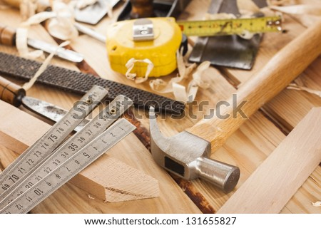 carpenter tools,hammer,meter,nails,shavings, and chisel over wood table - stock photo