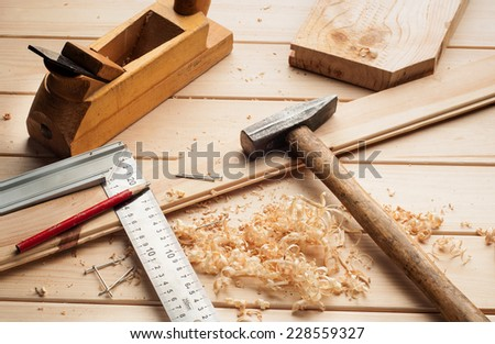 carpenter tools,hammer,meter, nails,shavings, and chisel over wood table - stock photo