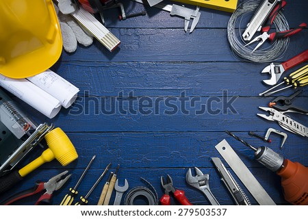 Carpenter Tools on Blue Wood.Blueprints are not subject to copyright. Words on them are regular like kitchen, bedroom, bathroom etc. - stock photo