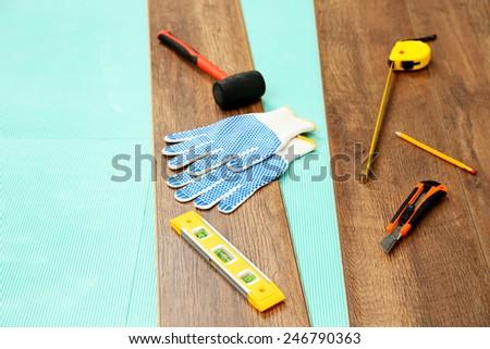 Carpenter tools on new laminate floor - stock photo