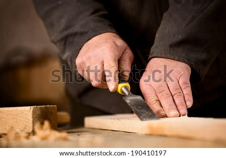 Carpenter using a chisel on a plank of wood to shape and cut a groove as he manufactures an article in his woodworking workshop, view of the hands and chisel - stock photo