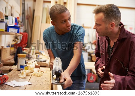 Carpenter With Apprentice Planing Wood In Workshop - stock photo