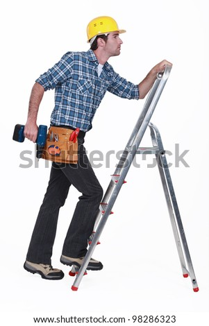 Carpenter with drill climbing step-ladder - stock photo