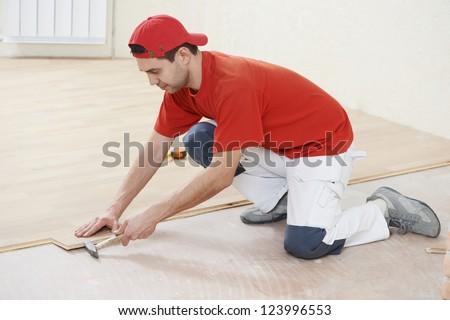 carpenter worker installing wood parquet board during flooring work with hammer - stock photo