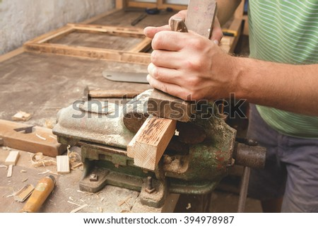 """Carpenter working hard in his small """"office"""". - stock photo"""