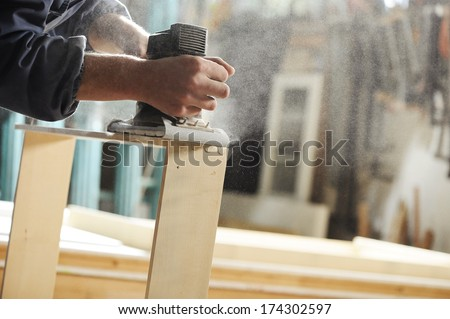 Carpenter working on a piece of furniture with a planer. - stock photo