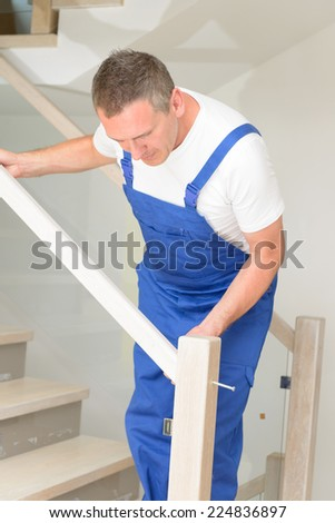 Carpenter working  on stairs - stock photo