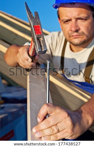Carpenter working on the roof structure - closeup, focus on large nail - stock photo