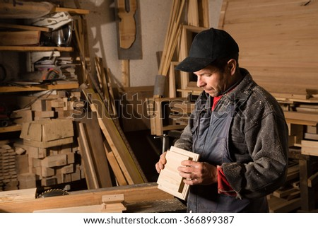 Carpenter works with wood in the carpentry workshop. Focus on wooden part. - stock photo