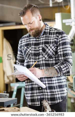 Carpenter writing at drawings in the workshop - stock photo