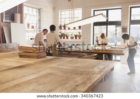 Carpenters making frames in their workshop - stock photo