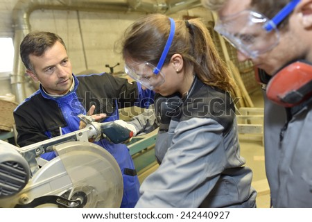 Carpentry teacher showing sawing machine to students - stock photo
