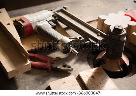 Carpentry tools - gun nailing and pliers lie on a workbench - stock photo