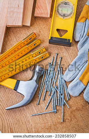carpentry tools nails claw hammer protective gloves level planks on wooden board - stock photo