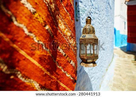 Carpet for sale and beautiful lantern on a street in Chefchaouen, Morocco, small town in northwest Morocco known for its blue buildings - stock photo