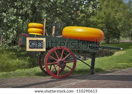 Carriage with cheese and a weighing machine - stock photo