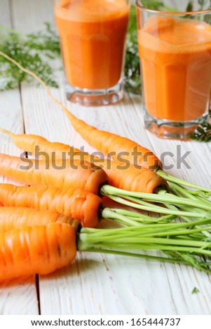 carrot on the table and two glasses of juice, food close up - stock photo
