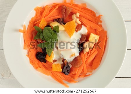 Carrot salad with dried fruits and natural yogurt - stock photo