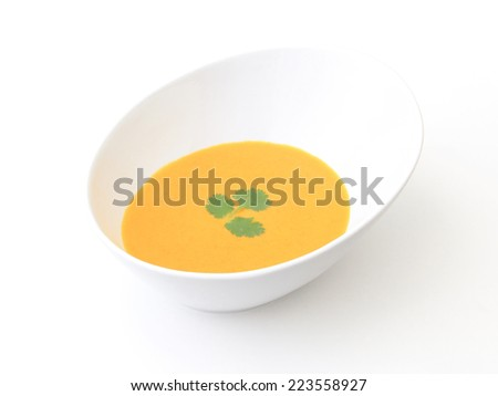 Carrot Soup - A bowl of carrot soup on a white background. - stock photo