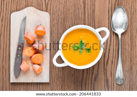 Carrot soup close up with fresh carrot, spoon and knife - stock photo