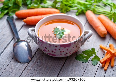 Carrot soup in a porcelain bowl  - stock photo