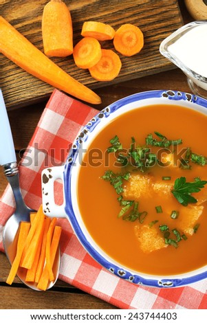Carrot soup  in bowl, on wooden background - stock photo