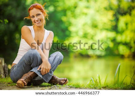 Carroty beautiful woman sitting on ground and dreams, on green park summer. - stock photo